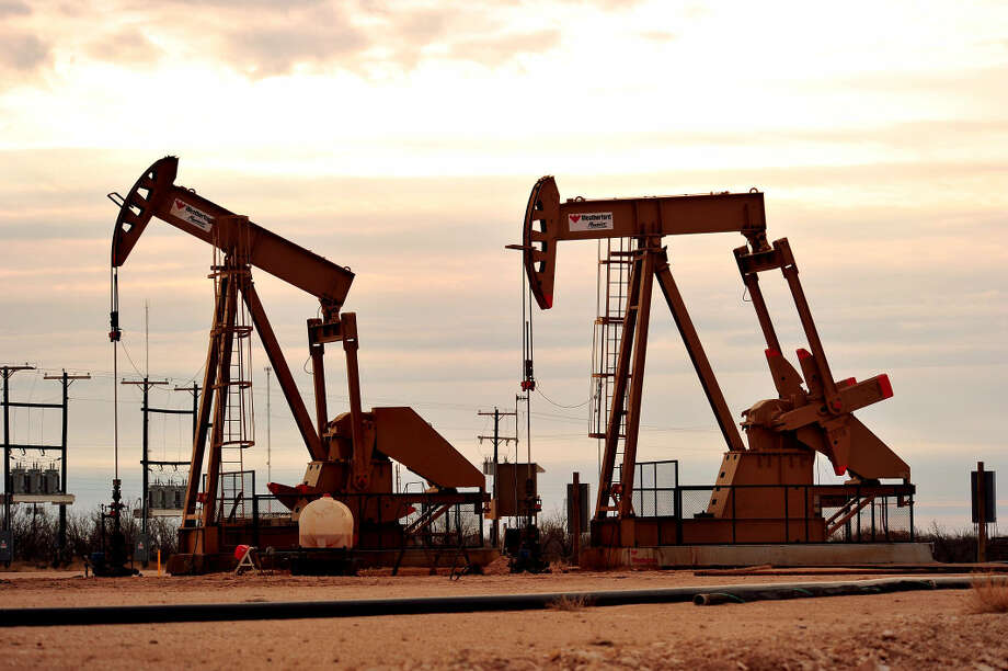 Kimberley Meyer/Special to the Houston Chronicle The rising sun and rugged terrain back drop Flex Rigs overlooking the small town of Big Lake Thursday morning, Jan. 8. Horizontal and Vertical rigs pepper the landscape while heavy equipment, people and truck traffic are overwhelming the small town's infrastructure. Photo: Kimberley Meyer