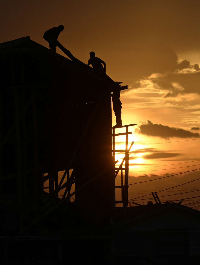 The sun sets behind workers at a home addition project near the intersection of W. New Jersey Ave. and Connell St. on Thursday, Sept. 10, 2015. James Durbin/Reporter-Telegram Photo: James Durbin