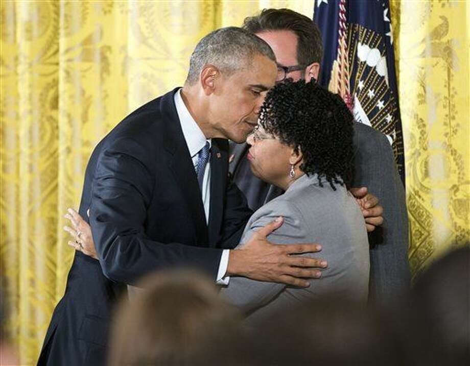 President Barack Obama embraces Jennifer Pinckney, wife of Reverend Clementa Pinckney, who was killed in the 2015 Charleston church shooting, after speaking in the East Room of the White House in Washington, Tuesday, Jan. 5, 2016, about steps his administration is taking to reduce gun violence. (AP Photo/Pablo Martinez Monsivais) Photo: Pablo Martinez Monsivais