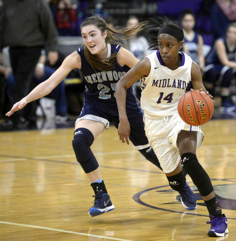 Midland's Alexis Washington (14) moves the ball against Greenwood's Cylie Mebane (25) on Wednesday, Dec. 30, 2015, at Midland High. James Durbin/Reporter-Telegram Photo: James Durbin