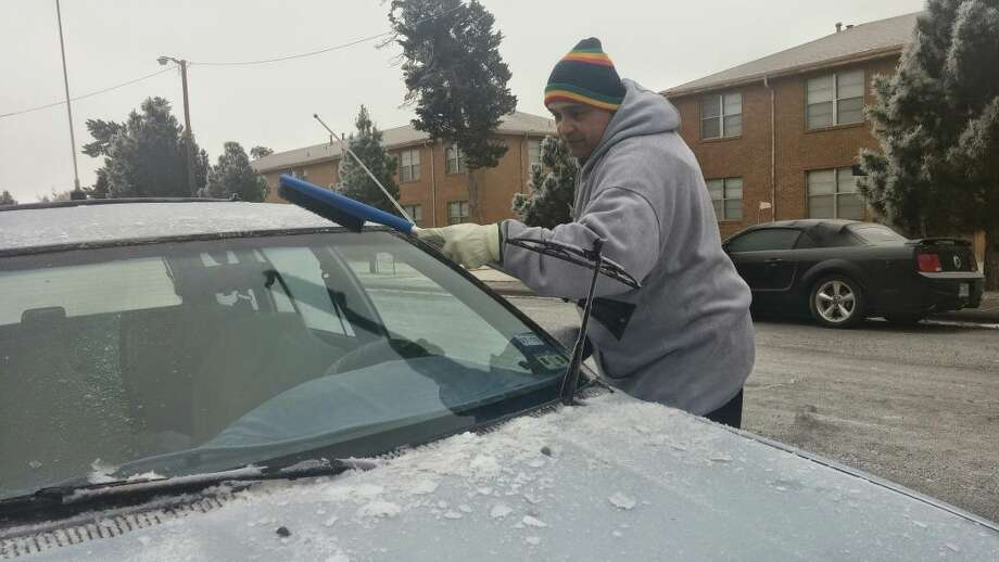 "Kia James scrapes the ice off his car Dec. 31, 2014, in central Midland. Although born in Hawaii, James said he spent many years in the north before moving to Odessa and later Midland. ""Texans can't drive in the ice,"" he said, noting they hit the brakes when they shouldn't but fail to slow down when they should on bridges and overpasses.  Photo: Rachael Gleason 