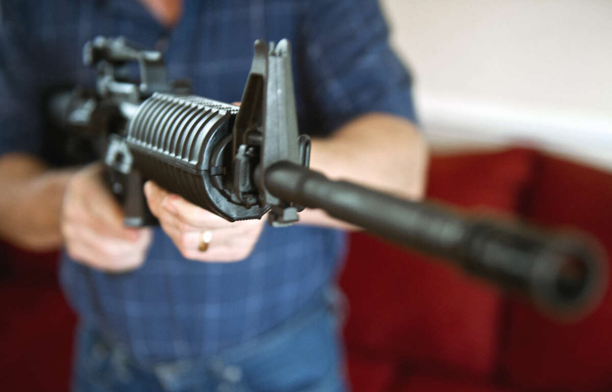 This February 4, 2013 photo illustration in Manassas, Virginia, shows a man holding a Colt AR-15 semi-automatic rifle.