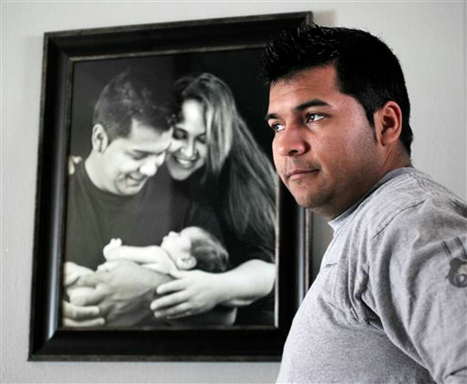 "FILE - In this Friday, Jan. 3, 2014 file photo, Erick Munoz stands with an undated copy of a photograph of himself, left, with wife Marlise and their son Mateo, in Haltom City, Texas. Munoz's attorneys said in a statement Wednesday, Jan. 22, 2014, that the fetus that Marlise Munoz is carrying has several ""abnormalities,"" including a deformation of the lower body parts that make it impossible to determine its gender. (AP Photo/The Fort Worth Star-Telegram, Ron T. Ennis, File) Photo: Ron T. Ennis / The Fort Worth Star-Telegram"