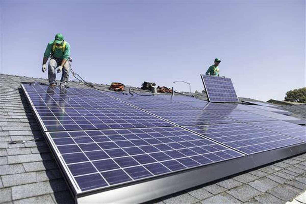 In this undated photo provided by SolarCity, workers install solar panels on the roof of a home. (AP Photo/Courtesy SolarCity)