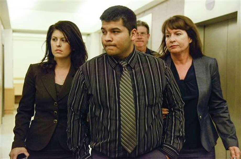 Erick Munoz, center, husband of Marlise Munoz is escorted by attorneys as he walks to 96th District Court Friday, Jan. 24, 2014 in Fort Worth, Texas. A judge has ordered a Texas hospital to remove life support for a pregnant, brain-dead woman. Judge R. H. Wallace Jr. issued the ruling Friday in the case of Marlise Munoz. John Peter Smith Hospital in Fort Worth has been keeping Munoz on life support against her family's wishes. Munoz was 14 weeks pregnant when her husband found her unconscious Nov. 26, possibly due to a blood clot. (AP Photo/Tim Sharp) Photo: TIM SHARP / FR62992 AP