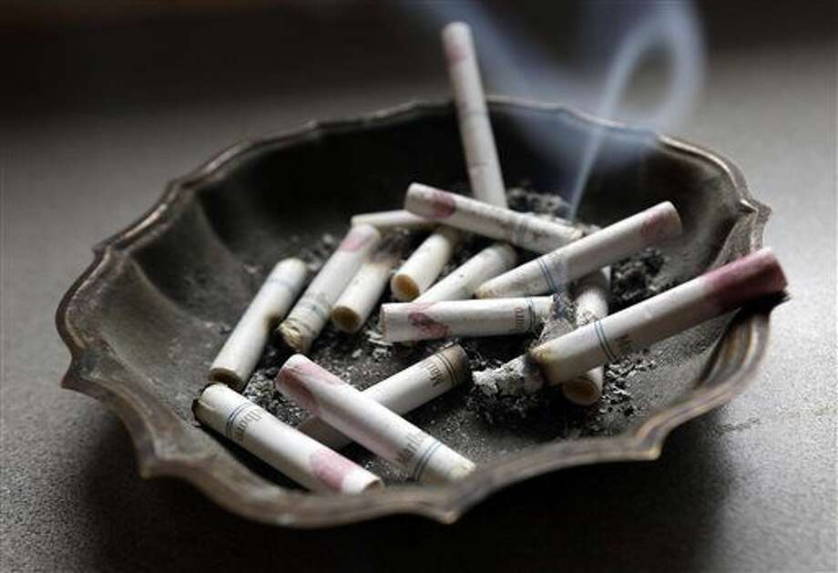 FILE - In this Saturday, March 2, 2013, photo, a cigarette burns in an ashtray at a home in Hayneville, Ala. A government study released on Monday, Jan. 11, 2016, shows that even though fewer U.S. teens are smoking, exposure to secondhand smoke remains a big problem. Nearly half of nonsmoking kids in middle school and high school were exposed to secondhand tobacco smoke in 2013, and rates were even higher among smokers. (AP Photo/Dave Martin) Photo: Dave Martin