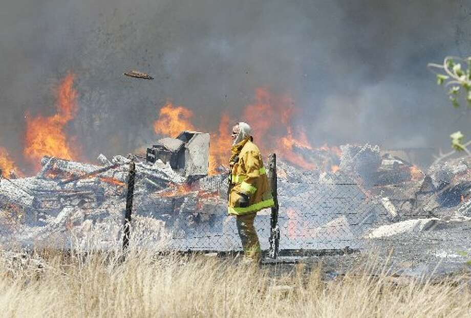 Midland Fire Fighter Robert Meggs walks away after tossing a piece of flammable debris into a contained fire at a grass fire. Photo: Reporter-Telegram
