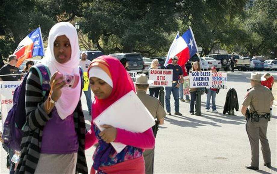 Amina Hassan, left, 11, of Grand Prairie, and Ayefa Klair, 10 of Irving, are faced with anti-Muslim protesters at the Texas Muslim Capitol Day in Austin, Texas, on Thursday, Jan. 29, 2015. Hundreds of Muslims from around Texas gathered for the Council on American-Islamic Relations rally and to talk to their representatives about legislation that's important to them. (AP Photo/Austin American-Statesman, Jay Janner) AUSTIN CHRONICLE OUT, COMMUNITY IMPACT OUT, INTERNET AND TV MUST CREDIT PHOTOGRAPHER AND STATESMAN.COM, MAGS OUT Photo: Jay Janner