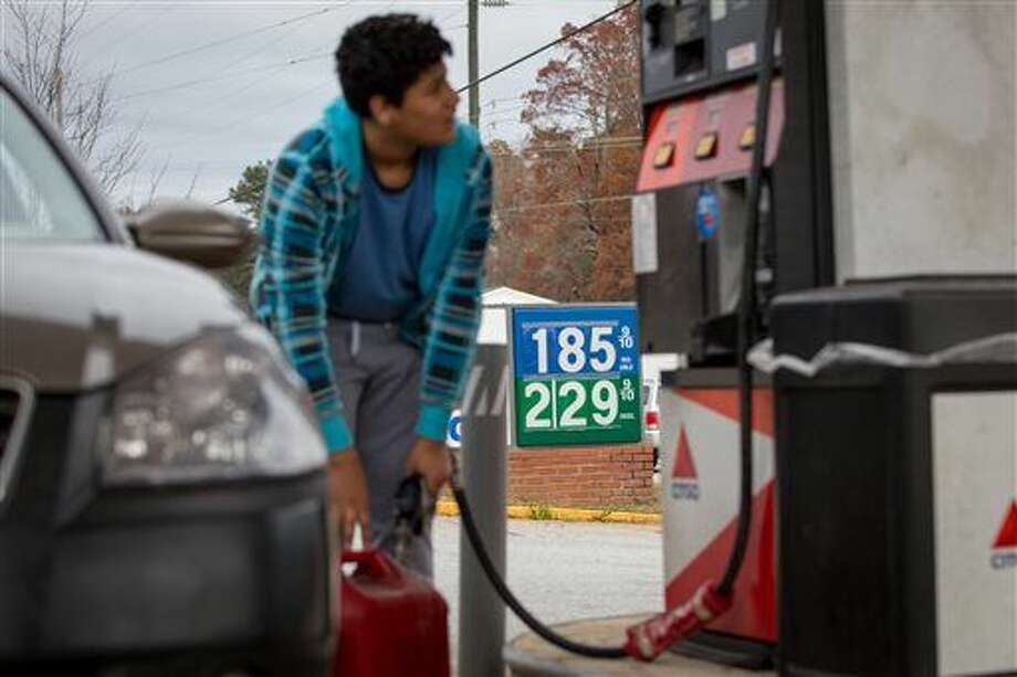 In this Wednesday, Nov. 25, 2015, photo, Cornelio Bonilla pumps gas at Best Food Mart gas station in Gainesville Ga. The price of oil continues to fall, extending a slide that has already gone further and lasted longer than most thought, and probing depths not seen since 2003. (AP Photo/Kevin Liles) Photo: Kevin Liles