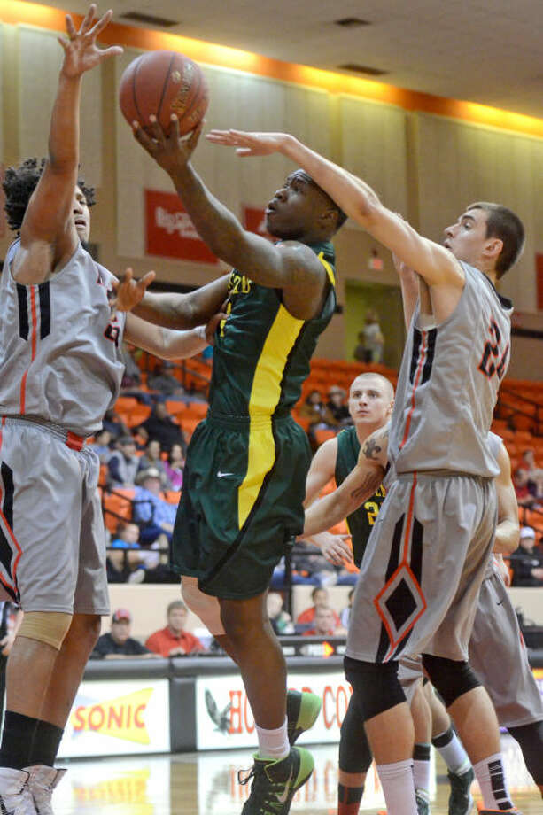 Midland College's Domonique Bull (4) goes up against Howard College's Demeco Blue (55) and Niels Bunschoten (24) on Thursday at Dorothy Garrett Coliseum in Big Spring. James Durbin/Reporter-Telegram Photo: JAMES DURBIN