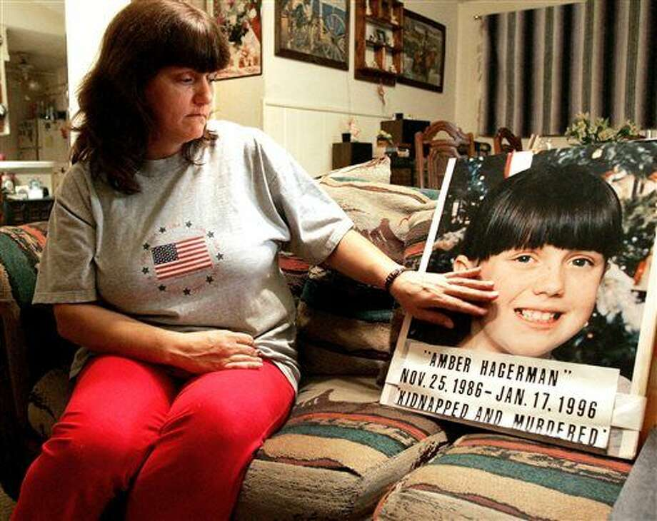 FILE - In this Jan. 12, 2006 file photo, Donna Norris touches a photo of her daughter, Amber Hagerman, at her Hurst, Texas, home. The 1996 slaying of the North Texas girl that led to the Amber Alert notification system to find missing children remains unsolved. Arlington police on Tuesday, Jan. 12, 2016, repeated their request for tips in finding the killer of the 9-year-old. Amber's mother, now named Donna Williams, appealed for justice for her daughter. (R. Jeena Jacob/Star-Telegram via AP) MAGS OUT; INTERNET OUT; MANDATORY CREDIT Photo: R. Jeena Jacob