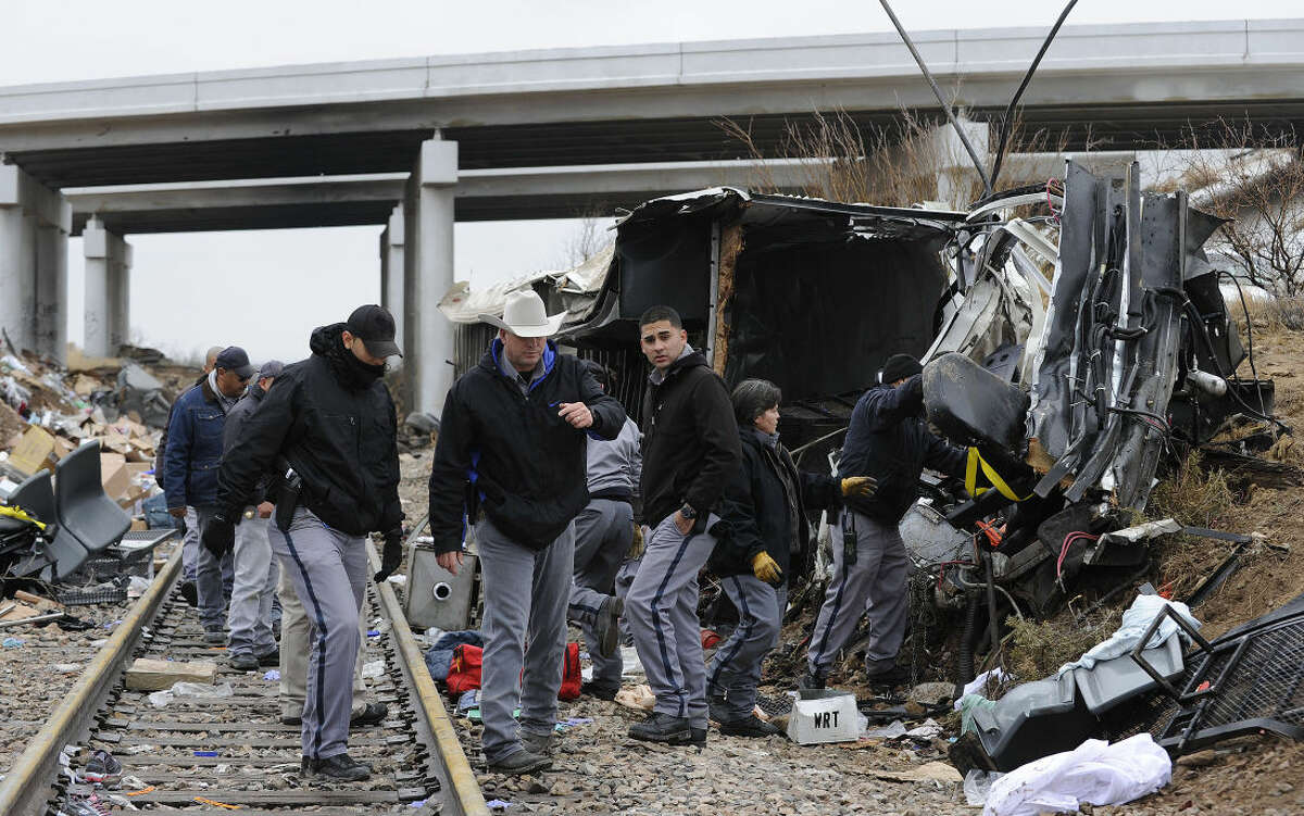 Investigators from multiple agencies survey the crash scene where a TDCJ transport bus lost control on Interstate 20, drove down an embankment and crashed into a moving train Wednesday morning, Jan. 14, 2015 near Penwell, Texas. 10 passengers on the bus died in the collision. (AP Photo/Odessa American, Mark Sterkel)