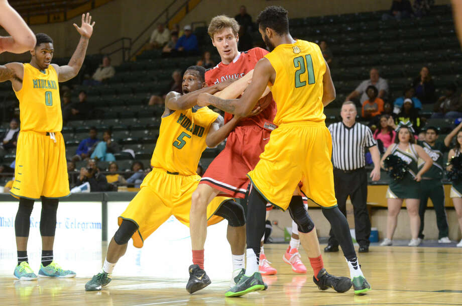Midland College's Maurice O'Field (5) and Jamal Evans (21) fight for possession of the ball against Howard College's Lis Shoshi (12) on Thursday, Jan. 29, 2015 at Chaparral Center. James Durbin/Reporter-Telegram