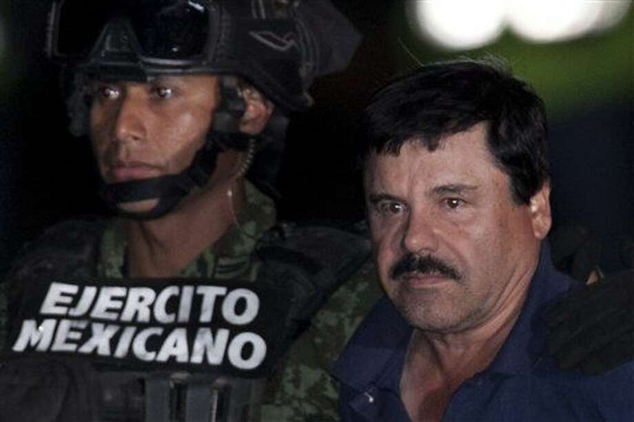 """Mexican drug lord Joaquin """"El Chapo"""" Guzman, right, is escorted by soldiers and marines to a waiting helicopter, at a federal hangar in Mexico City, Friday, Jan. 8, 2016. The world's most wanted drug lord was recaptured by Mexican marines Friday, six months after he fled through a tunnel from a maximum security prison in an escape that deeply embarrassed the government and strained ties with the United States.(AP Photo/Marco Ugarte)"""