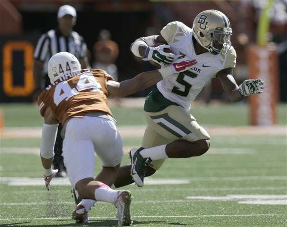 Baylor's Antwan Goodley (5) runs around Texas defender Dylan Haines (44) during the first half of an NCAA college football game, Saturday, Oct. 4, 2014, in Austin, Texas. (AP Photo/Eric Gay) Photo: Eric Gay