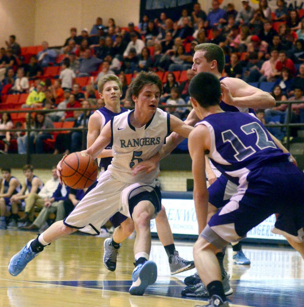 Greenwood's Grant Franklin (5) drives against Abilene Wylie's Zach Erickson (12) and Christian Nichols (24) on Friday at Greenwood High School. James Durbin/Reporter-Telegram