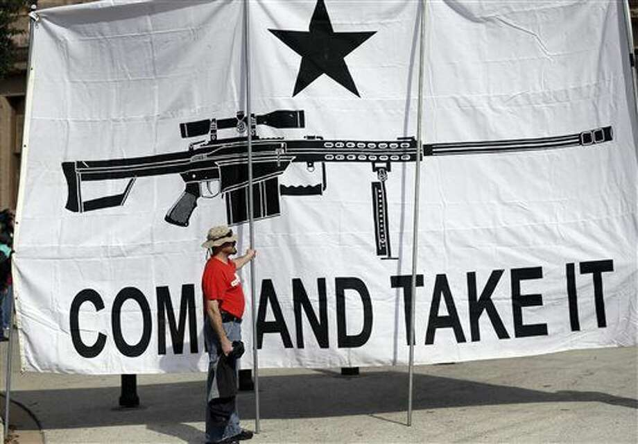 "A demonstrator helps hold a large ""Come and Take It"" banner at a rally in support of open carry gun laws at the Capitol, Monday, Jan. 26, 2015, in Austin, Texas. (AP Photo/Eric Gay) Photo: Eric Gay"
