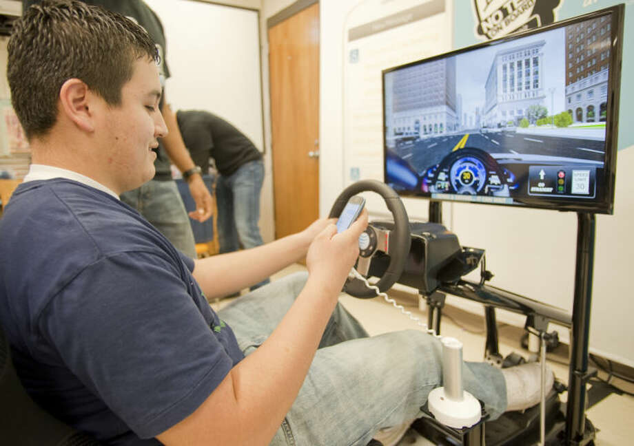 Midland High sophomore Jose Munoz tries to drive the simulator while texting Wednesday during an educational seminar, put on by AT&T, to demonstrate the dangers of texting while driving. Tim Fischer\Reporter-Telegram Photo: Tim Fischer