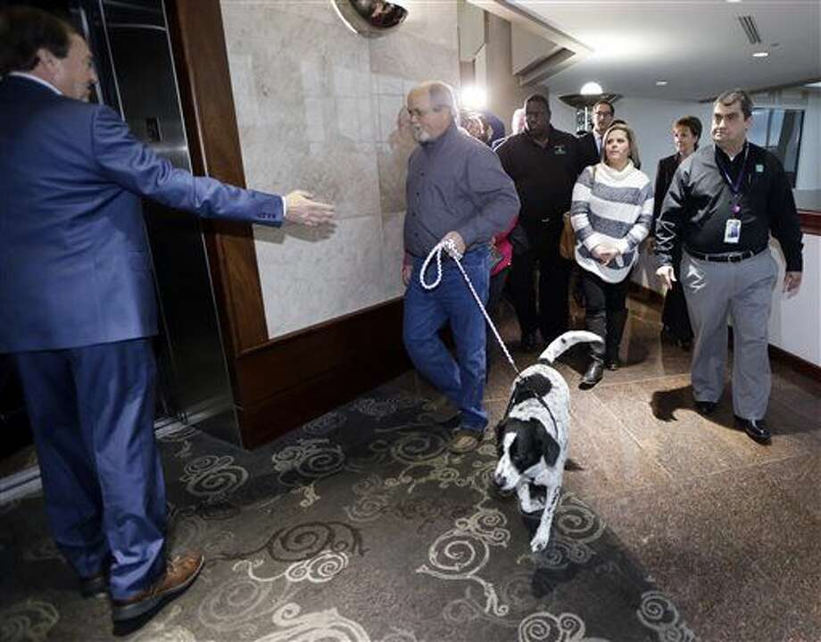 John Robinson leads the family dog as he walks to an elevator at the Tennessee Lottery headquarters, Friday, Jan. 15, 2016, in Nashville, Tenn. The Robinsons claim to have one of the winning tickets in the record $1.6 billion jackpot drawing that took place Wednesday. (AP Photo/Mark Humphrey) Photo: Mark Humphrey
