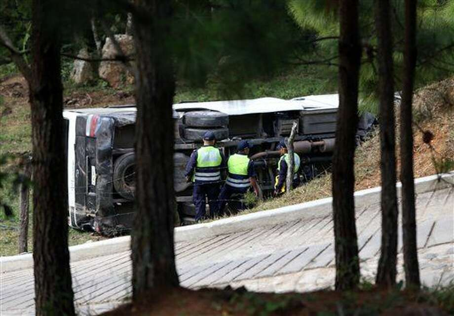 This photo courtesy of El Heraldo de Honduras newspaper shows a bus on its side along the highway between the town of San Juancito and the capital city of Tegucigalpa, Honduras, Wednesday, Jan. 13, 2016. Two New York college students and a U.S. health-care worker died Wednesday in this Central American nation when their bus crashed while taking them to the airport to fly home after a volunteer mission helping poor Hondurans. (El Heraldo de Honduras via AP) Photo: HONS