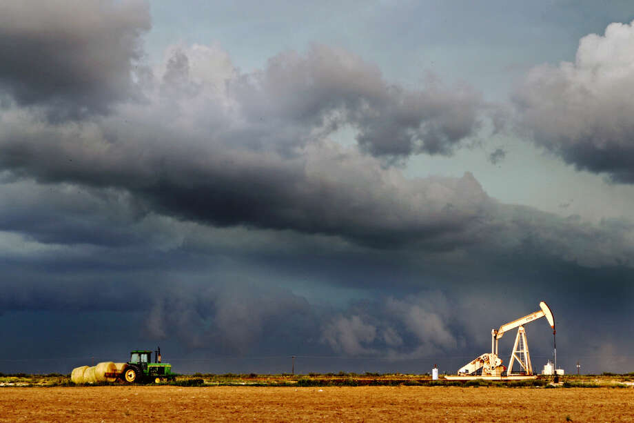 A hay farmer stacks bales near Highway 349 north of the Martin County Line as a severe thunderstorm develops, Saturday, May 23, 2015. Rain and high winds swept through the Permian Basin Saturday evening. James Durbin/Reporter-Telegram Photo: James Durbin
