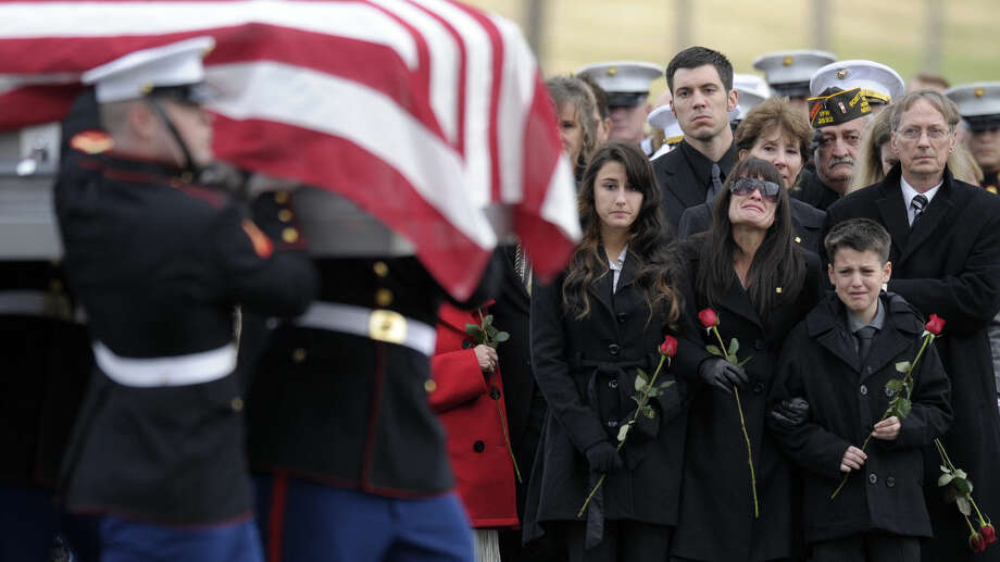 Catherine Stouffer, flanked by her children, Shannon, 17 and Shane, 12, watches as the casket of her husband Marine Chief Warrant Officer 3 Gary L. Stouffer, of Hubert, N. C., is carried to the burial site, Friday, Dec. 7, 2012, at Arlington National Cemetery in Arlington, Va. Stouffer, 37, was among four veterans killed when the float they were on was hit by a train during a parade in Midland, Texas on Nov. 15. (AP Photo/Susan Walsh) Photo: Susan Walsh