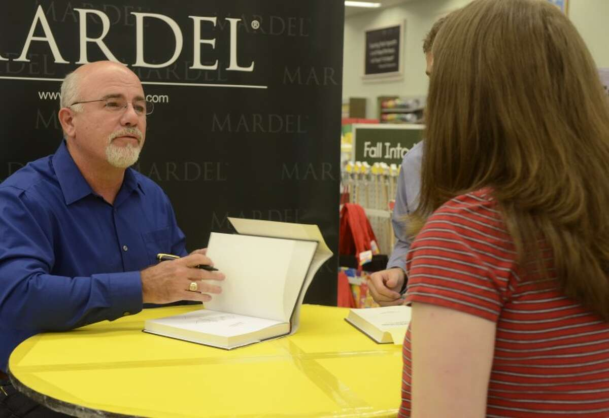 """Dave Ramsey talks to Alecia Simpson while signing a copy of his book, """"EntreLeadership,"""" Thursday evening at Mardel."""