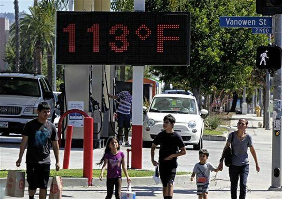 FILE - In this Aug. 15, 2015 file photo, pedestrians walk past a digital thermometer reading 113 degrees Fahrenheit in the Canoga Park section of Los Angeles. Earth last year wasn't just the hottest year on record, but it left a century of temperature high marks in its hot dust. The National Oceanic Atmospheric Administration (NOAA) and NASA announced Wednesday, Jan. 20, 2016, that 2015 was by far the hottest year in 136 years of record keeping. (AP Photo/Richard Vogel, File) Photo: Richard Vogel