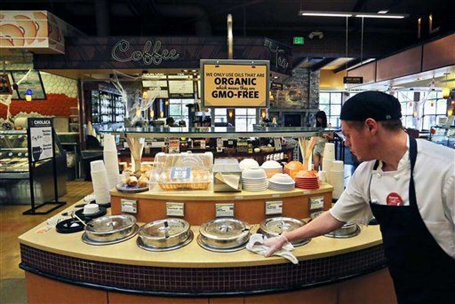 FILE - In this Oct. 23, 2014 file photo, a grocery store employee wipes down a soup bar with a display informing customers of organic, GMO-free oils, in Boulder, Colo. A large majority of Americans support labeling of genetically modified foods, whether they care about eating them or not. According to a December Associated Press-GfK poll, 66 percent of Americans favor requiring food manufacturers to put labels on products that contain genetically modified organisms, or foods grown from seeds engineered in labs. Only seven percent are opposed to the idea, and 24 percent are neutral. (AP Photo/Brennan Linsley, File) Photo: Brennan Linsley