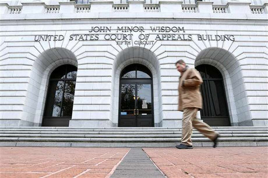 A man walks in front of the 5th U.S. Circuit Court of Appeals, Wednesday, Jan. 7, 2015, in New Orleans. The federal appeals court in New Orleans is considering whether a Texas law puts up an unconstitutional obstacle to women seeking abortions. (AP Photo/Jonathan Bachman) Photo: Jonathan Bachman