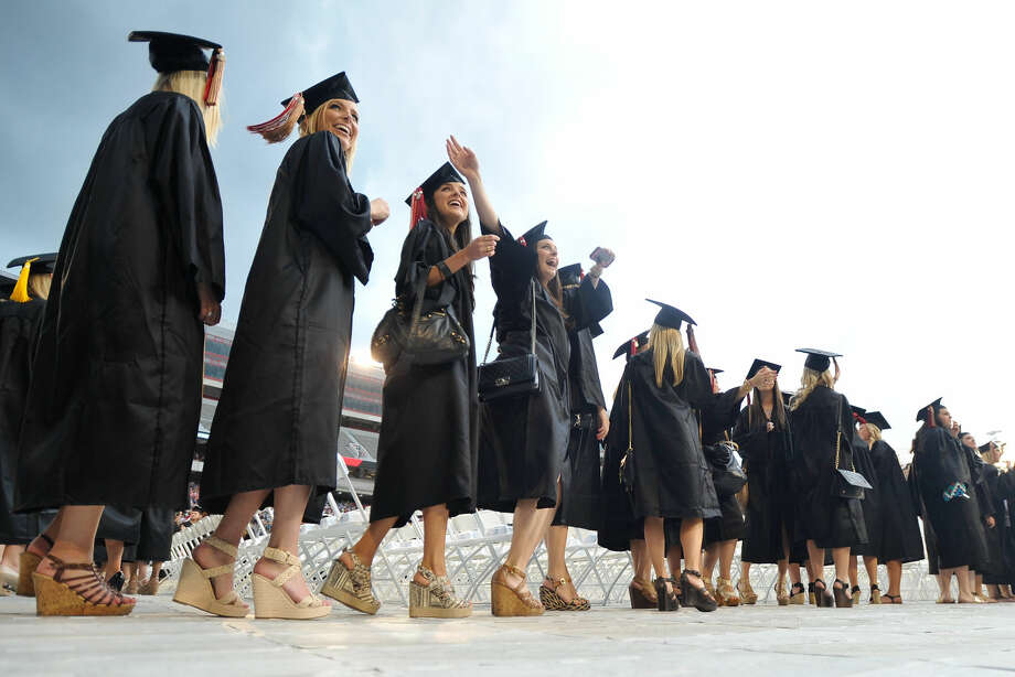 In this May 9, 2014 file photo, graduates cheer during the processional portion of the spring commencement ceremony at the University of Georgia in Athens, Ga. University students who graduated this past spring and used loans to pay for their education will face their first bill in coming weeks as the six-month grace period on federal and private education loans winds down. (AP Photo/Athens Banner-Herald, AJ Reynolds, File) Photo: AJ Reynolds