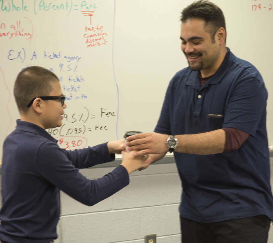 Tony Morin delivers a cup of coffee to Eric Lucero, 7th grade math instructor at Abell Junior High Thursday 01-14-16, as part of the Life Skills class and learning to brew coffee, charge money or apply a charge to a tab teachers can run. Tim Fischer/Reporter-Telegram Photo: Tim Fischer