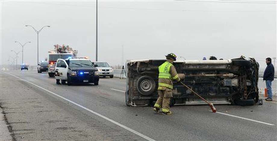 Emergency personal attend to the scene of an accident were the driver of a truck was not injured Tuesday, Dec. 30, 2014, on Highway 191 in Odessa, Texas. (AP Photo/Odessa American, Mark Sterkel) Photo: Mark Sterkel