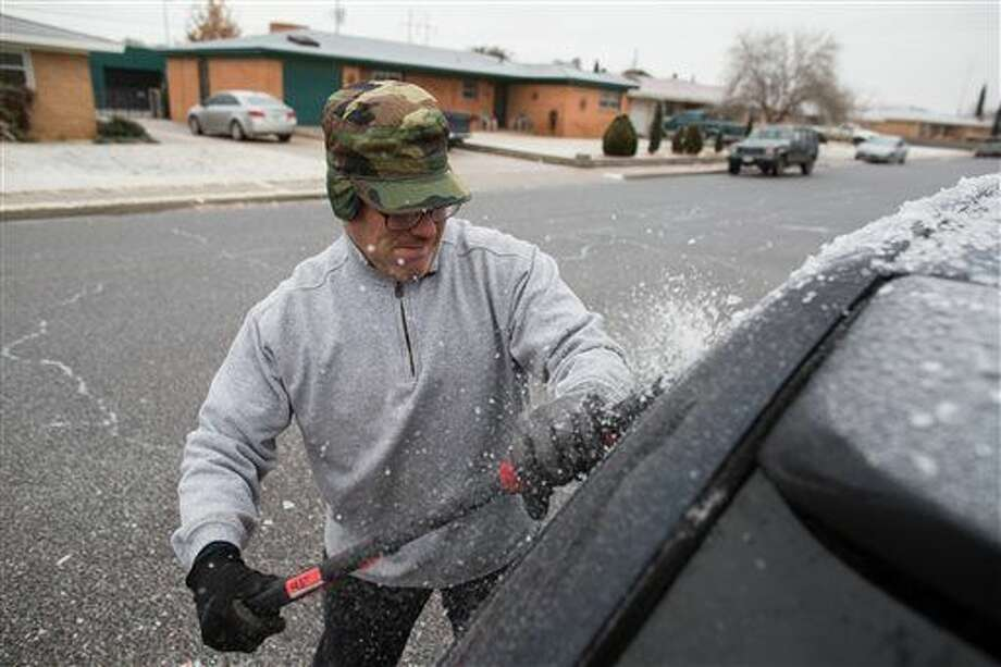 Guy Harned removes ice from his car after an overnight ice storm in Odessa, Texas, Wednesday, Dec. 31, 2014. (AP Photo/The Odessa American, Courtney Sacco) Photo: Courtney Sacco