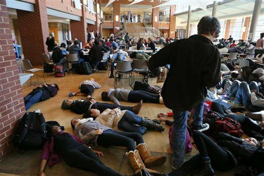 FILE - In this Dec. 1, 2014 file photo, students participating in a die lie on the cafeteria floor at Clayton, Mo., High School following a grand jury's decision not to indict a white police officer who killed 18-year-old black Michael Brown. The American Civil Liberties Union filed the lawsuit Monday, Jan. 5, 2015 on behalf of a jury member asking a Missouri court to remove a lifetime order that prevents jurors from discussing the case. (AP Photo/St. Louis Post-Dispatch, Cristina Fletes-Boutte, File) Photo: Cristina Fletes-Boutte