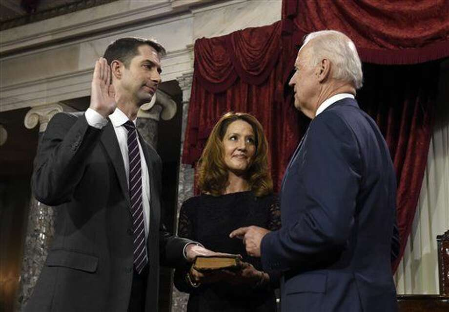 Vice President Joe Biden administers the Senate oath to Sen. Tom Cotton R-Ark., during a ceremonial re-enactment swearing-in ceremony, Tuesday, Jan. 6, 2015, in the Old Senate Chamber on Capitol Hill in Washington. Cotton's wife Anna is at center. (AP Photo/Susan Walsh) Photo: Susan Walsh