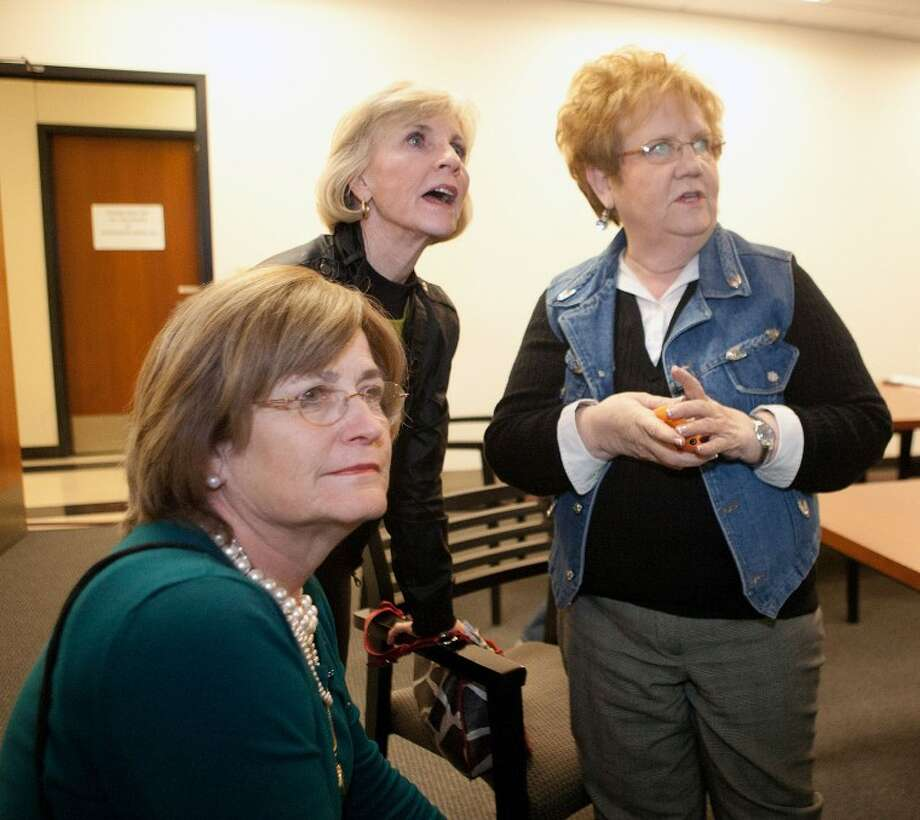 Midland Independent School District Trustee, District 5 incumbent Karen Nicholson, from left, Midland College trustee, Precinct 2 challenger Jan Artley, and President of the League of Women Voters, Mary Smith, look at voting results as they are posted at the Midland County Annex in this file photo.