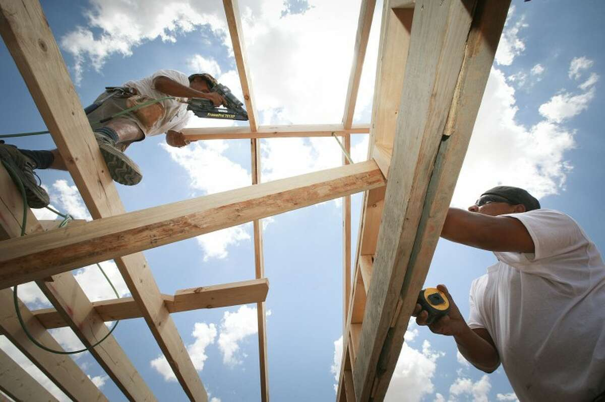 (File Photo) Rafael Rodriguez, left, nails a rafter to a ridge board as Joe Ramirez Jr. measures the roofs rise Friday at a new home construction site located on the 1400 block of E. Jax Ave. Cindeka Nealy/Reporter-Telegram