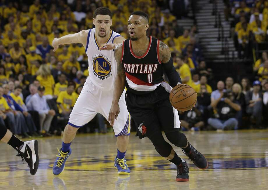 Trail Blazers guard Damian Lillard dribbles past the Warriors' Klay Thompson during the first half of Game 2 at Oracle Arena. Photo: Marcio Jose Sanchez, Associated Press