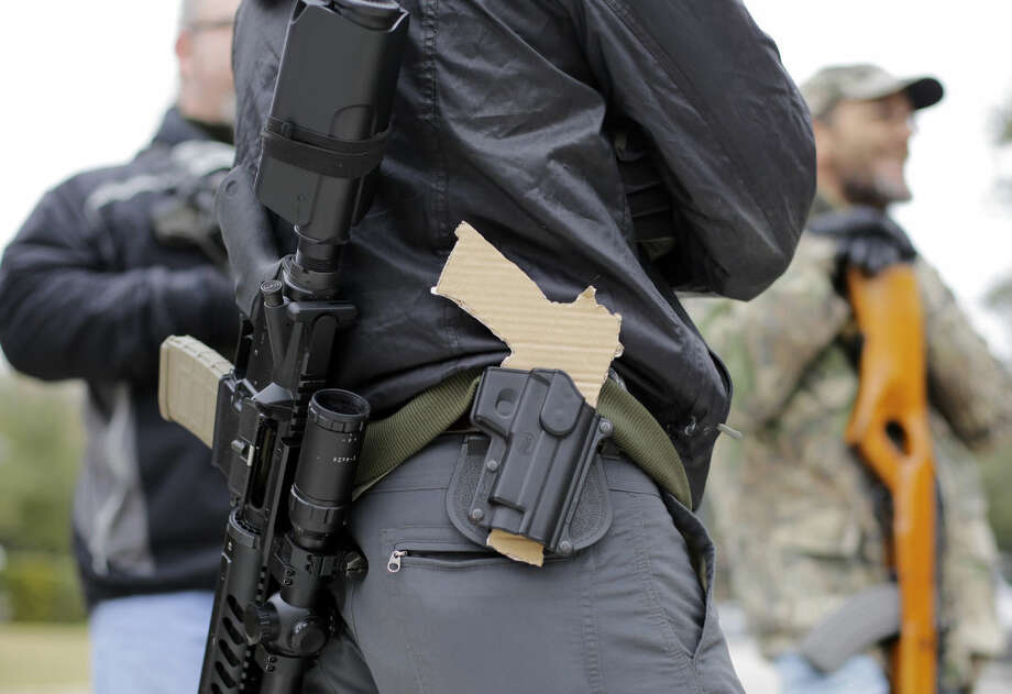 FILE - In this Jan. 13, 2015, file photo, a gun-rights advocate carries a rifle on his back and a cardboard cutout of a pistol on his waist as a group protests outside the Texas Capitol, in Austin, Texas. Texas lawmakers on Friday, May 29, 2015, approved carrying handguns openly on the streets of the nation's second most-populous state, sending the bill to Republican Gov. Greg Abbott, who is expected to sign it and reverse a ban dating to the post-Civil War era. (AP Photo/Eric Gay, File)