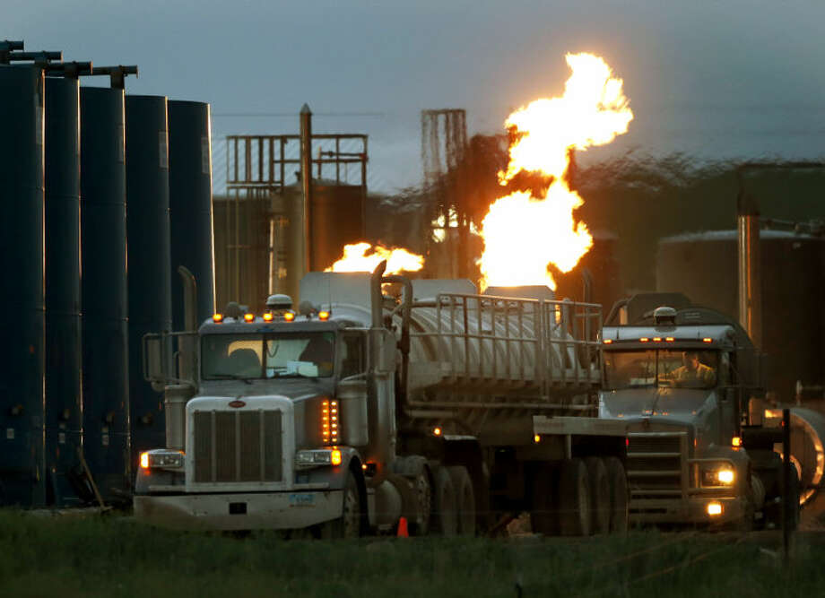 In this June 9, 2014 photo, drivers and their tanker trucks, capable of hauling water and fracturing liquid line up near a natural gas burn off flame and storage tanks in Williston, N.D. The epicenter of the oil boom is a 45-mile stretch of U.S. Route 85 in North Dakota between the towns of Williston and Watford City. (AP Photo/Charles Rex Arbogast) Photo: Charles Rex Arbogast