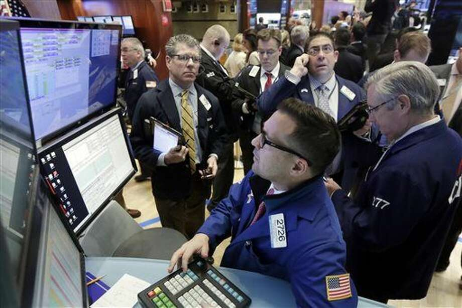 Specialist Paul Cosentino, foreground, works with traders at his post on the floor of the New York Stock Exchange, Wednesday, Jan. 27, 2016. Stocks are opening broadly lower as energy companies take another tumble and after Apple predicted its first sales decline in 13 years. (AP Photo/Richard Drew) Photo: Richard Drew