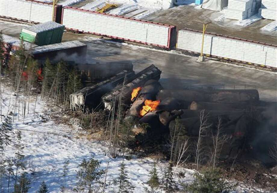 This aerial photo shows derailed train cars burning in Plaster Rock, New Brunswick on Wednesday, Jan. 8, 2014. A Canadian National Railway freight train carrying crude oil and propane derailed Tuesday night in a sparsely populated region of northwestern New Brunswick. More than 100 residents remained evacuated from their homes. There were no deaths or injuries. (AP Photo/The Canadian Press, Tom Bateman) Photo: Tom Bateman / The Canadian Press