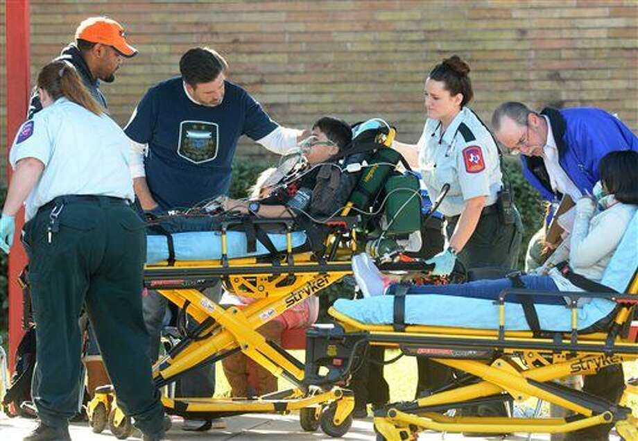 Jeremy Robison watches as his son Raj Robison is wheeled to a waiting ambulance Thursday, Jan. 28, 2016, after an alleged carbon monoxide leak at Marshall Middle School in Beaumont, Texas, began making students ill. Several dozen students and adults were transported to area hospitals from the event. (Guiseppe Barranco/The Beaumont Enterprise via AP) Photo: Guiseppe Barranco
