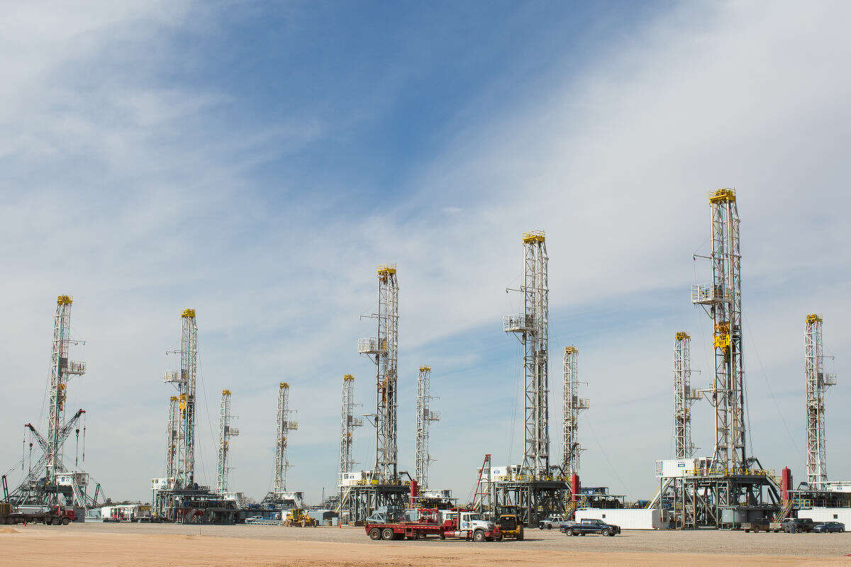 This photo shows a number of oil drilling rigs stacking in Helmerich & Payne International Drilling Company's yard in Ector County, Texas, Monday, Jan. 26, 2015. (AP Photo/Odessa American, Courtney Sacco)