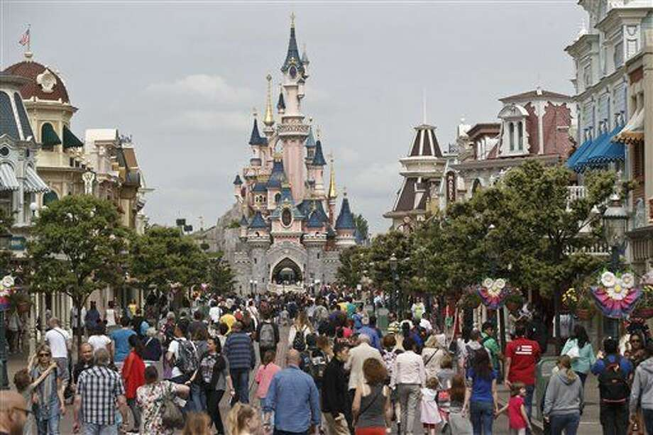 FILE - This Tuesday, May 12, 2015 file photo shows visitors walking toward the Sleeping Beauty's Castle, background, at Disneyland Paris in Marne la Vallee, east of Paris, France. A French police official says a man found to be carrying two handguns has been arrested at a hotel at Disneyland Paris. France remains under a state of emergency since Nov. 13 Islamic extremist attacks around Paris that killed 130 people. (AP Photo/Michel Euler, File) Photo: Michel Euler