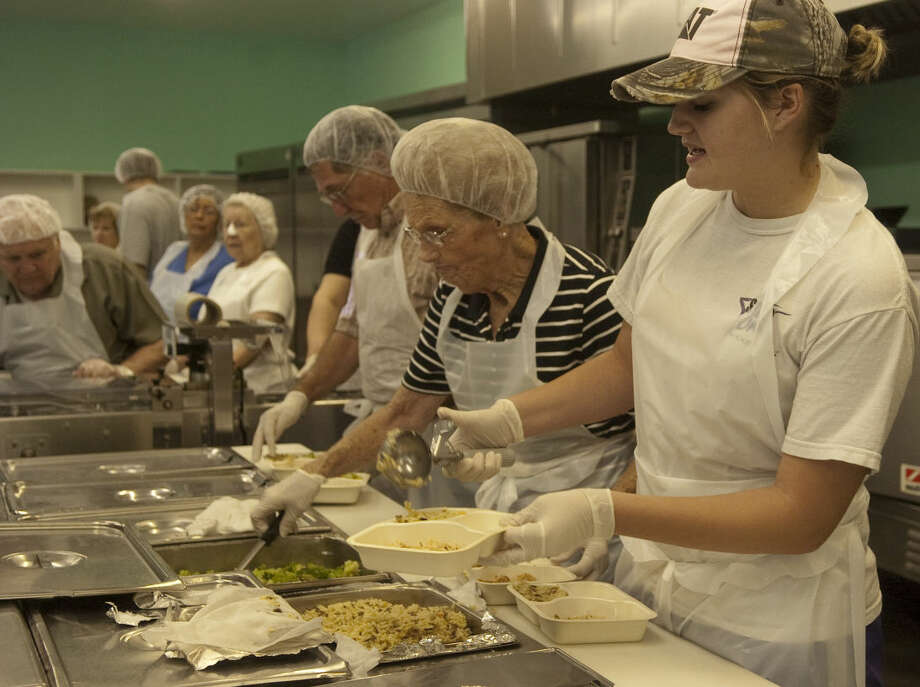 Lindsay Leible fills plates in the Meals on Wheels kitchen as she and other volunteers help put the hot meals together in this MRT file photo. Photo: Tim Fischer