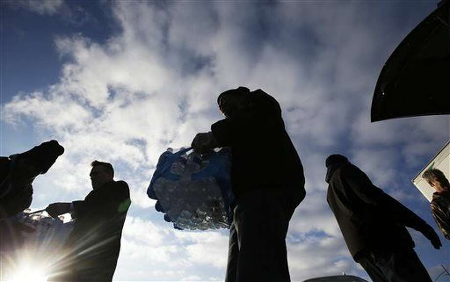 Midwest Food Bank workers and volunteers carry cases of water that was donated, Wednesday, Jan. 27, 2016, in Indianapolis. All of the water that was collected will be sent to Flint, Mich., where drinking water has been contaminated by lead. (AP Photo/Darron Cummings) Photo: Darron Cummings
