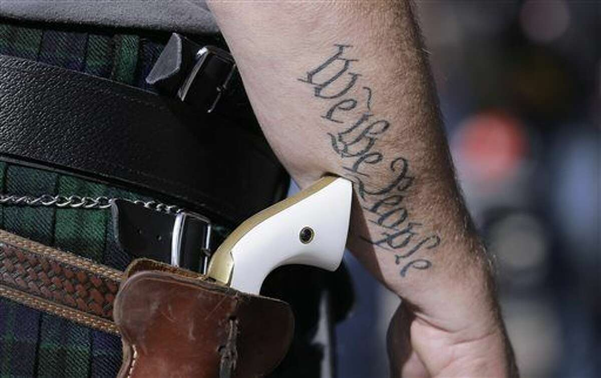 Scott Smith, a supporter of open carry gun laws, wears a pistol as he prepares for a rally at the Capitol, Monday, Jan. 26, 2015, in Austin, Texas. (AP Photo/Eric Gay)