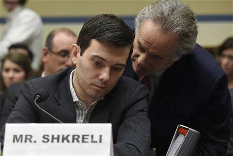 Pharmaceutical chief Martin Shkreli, left, huddles with his attorney Benjamin Brafman on Capitol Hill in Washington, Thursday, Feb. 4, 2016, during the House Committee on Oversight and Reform Committee. Shkreli refused to testify before U.S. lawmakers who excoriated him over severe hikes for a drug sold by a company that he acquired. (AP Photo/Susan Walsh) Photo: Susan Walsh
